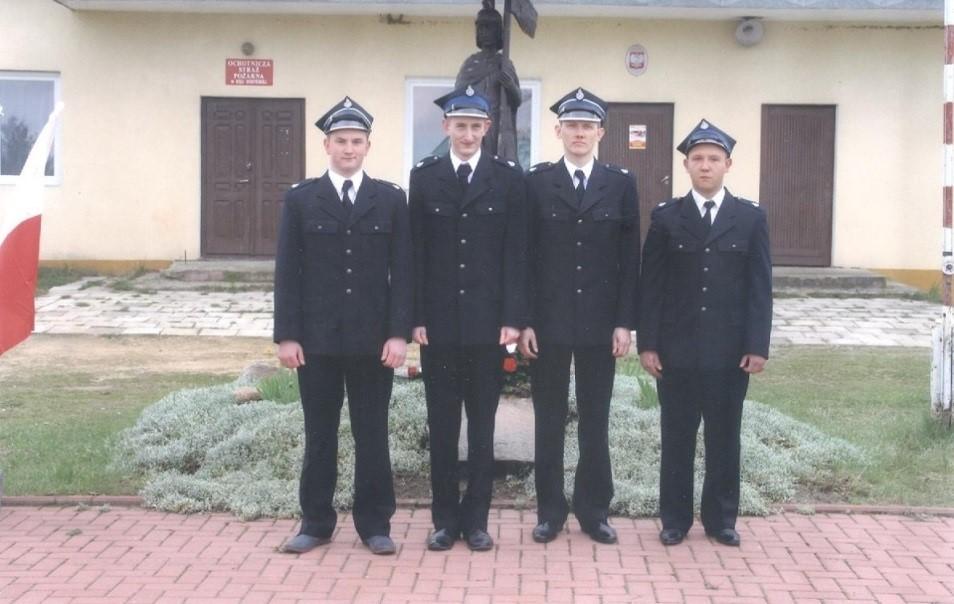 czterech strażaków pred budynkiem w szeregu