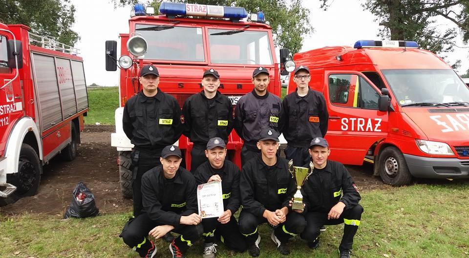 strażacy przed wozem strażackim