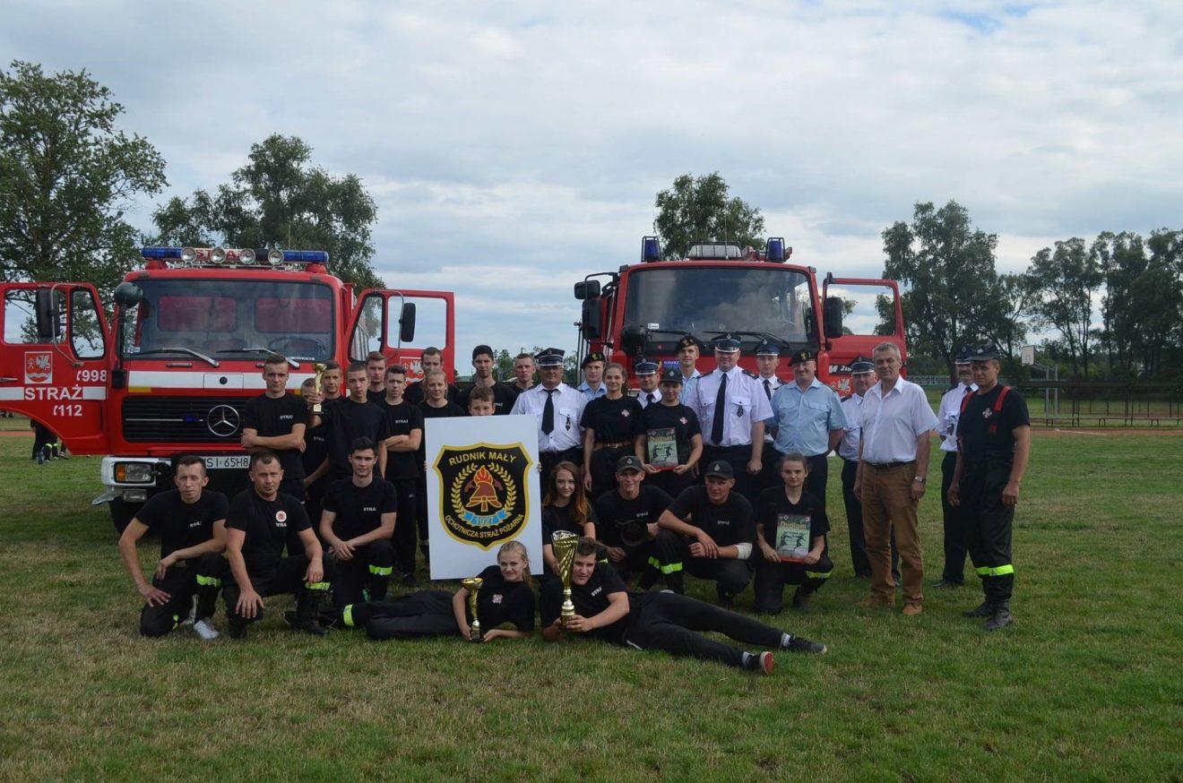 grupa strażaków przez wozami strażackimi